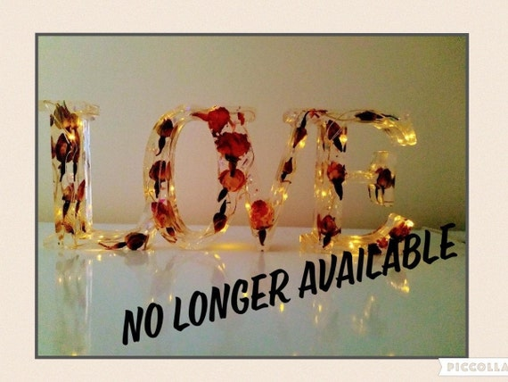 Beautiful resin love sign with real rosebuds and fairy lights in soft white