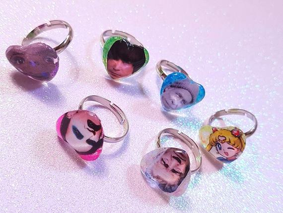 Faces icons glitter ring ( adjustable ) heart shaped background glitter Bukowski, Sailor Moon, E.T. and John Lennon.