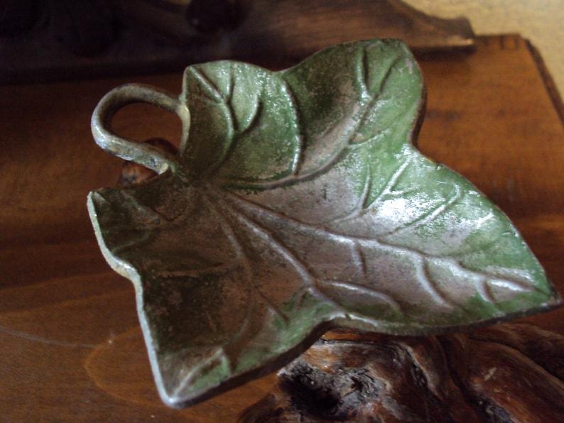 Mounted on a grape vine corkscrew leaf shaped ashtray.
