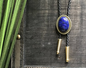 vintage vinyl black and brown braided bolo tie and gold metal slide with blue lapis faux gemstone arrowhead and tarnished tips
