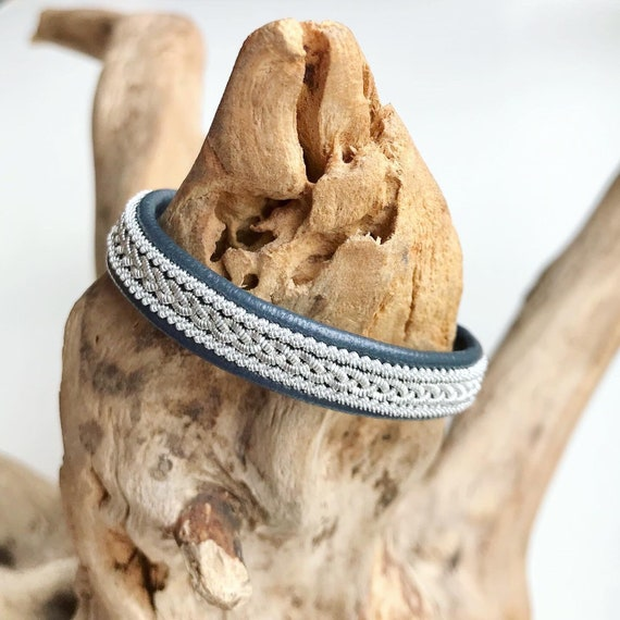 Sami traditional charcoal blue reindeer leather bracelet with borders and a pewter button.