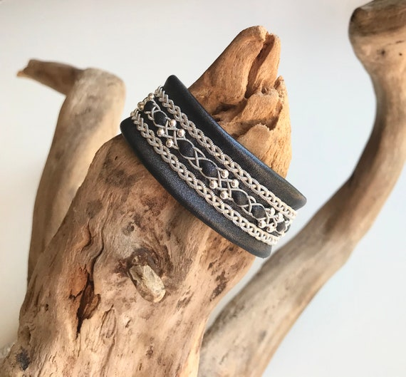 Traditional Sami leather cuffs, with three braids of spun pewter and sterling silver beads. The borders with flat pewter threads.