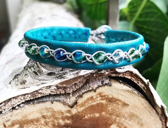 Teal reindeer leather bracelets with blues, turquoise and green Swarovski crystals.