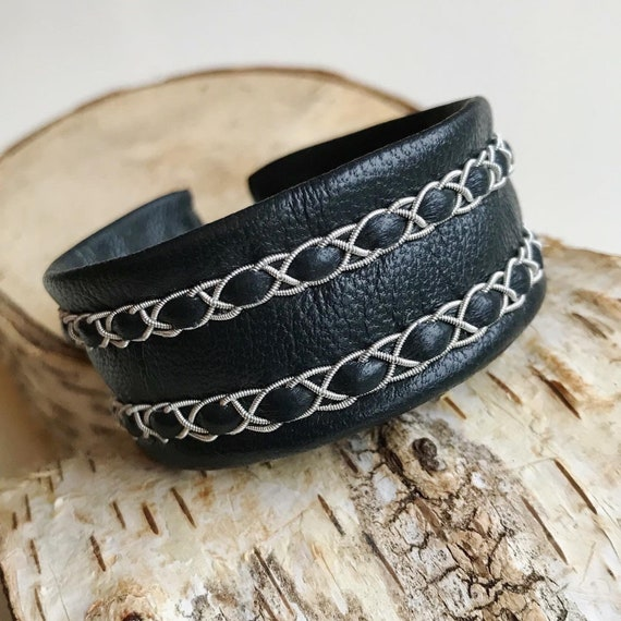 Scandinavian bracelet with thin Sami braids on a reindeer leather cuff.