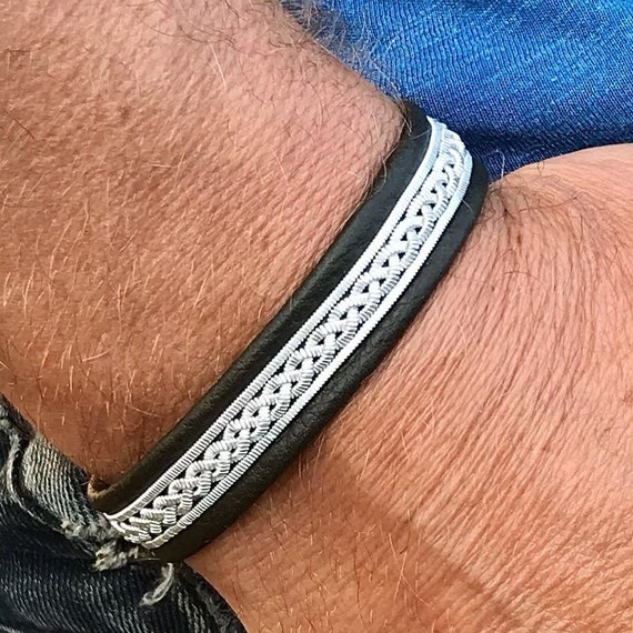 Sami leather bracelets with a braid of wider flat pewter threads and borders.