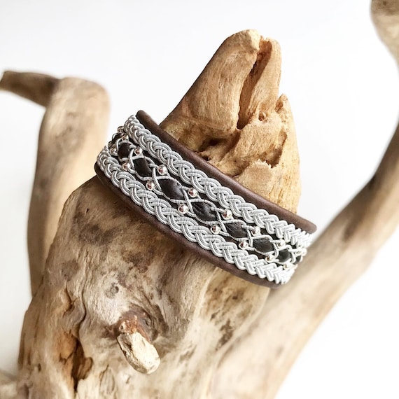 Scandinavian reindeer leather bracelet with a sterling silver beads row and traditional braids.