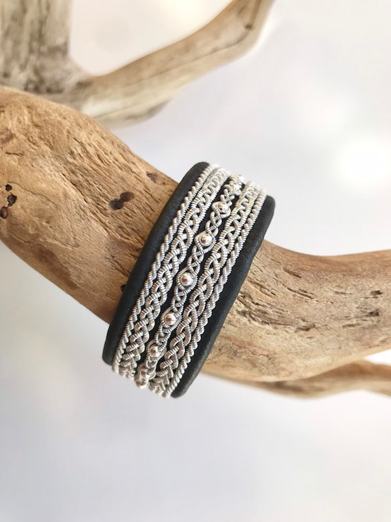 Wide black Scandinavian reindeer leather bracelets, with traditional pewter braiding, sterling silver beads and twisted borders.