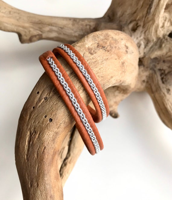 Traditional Sami reindeer leather bracelets, in tan with a braid of flat pewter threads.