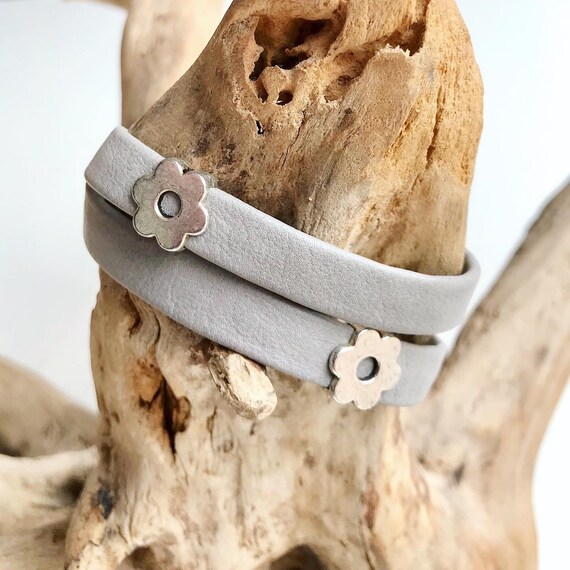 Light grey wrap around reindeer leather bracelets with a magnetic clasp and two flower sliders.