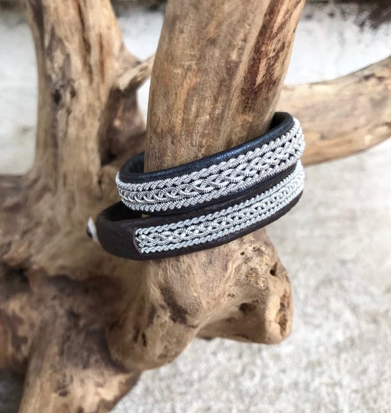 Traditional Sami reindeer leather bracelets with a braid of flat pewter threads and borders. Black, navy or metallic black.