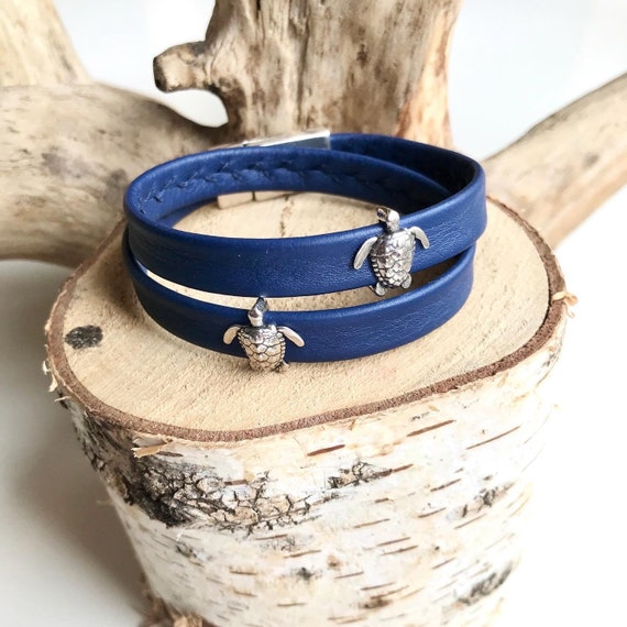 Blue wrap around reindeer leather bracelets with a magnetic clasp and turtle sliders.