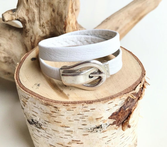 White wrap around reindeer leather bracelets with a magnetic belt clasp.
