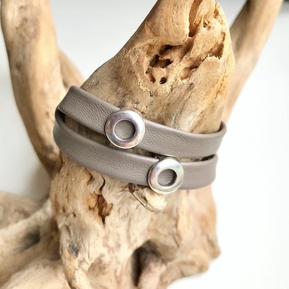 Wrap around reindeer leather bracelet with a magnetic clasp and two circular silver sliders.