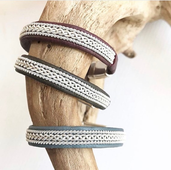 Sami reindeer leather bracelets with a braid of flat pewter threads and borders. Grey-blue, dark brown and deep maroon.