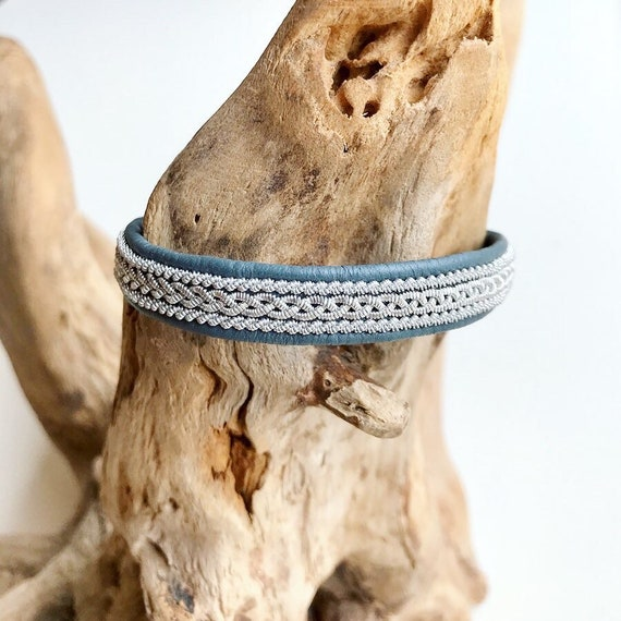 Traditional Sami grey blue reindeer leather bracelet with borders and a magnetic clasp.