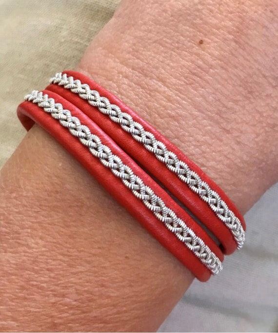 Traditional Sami double reindeer leather bracelets, with a braid of flat pewter threads.