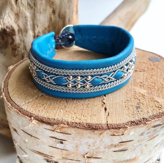 Wide cyan blue reindeer leather bracelet with traditional pewter braiding, sterling silver beads and twisted borders.