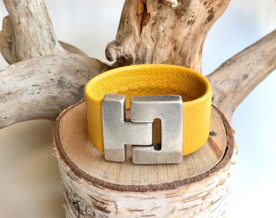 Yellow leather cuff with a magnetic clasp.