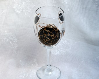 Galaxy - Black and Gold - An exclusive design, hand painted, wine glass featuring black 'planets' swirled with raised gold 'orbit trails'