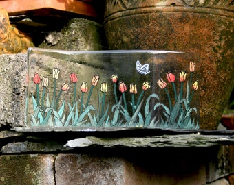 """Tulip Garden.  A row of tulips with a flitting butterfly. A hand painted, fused glass free standing 'wave'  Approx. 10 x 25 cm (4 x 10"""")"""