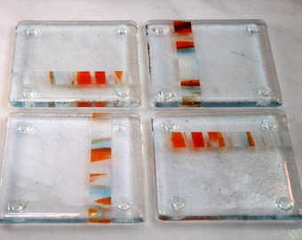 Fused glass coasters 'Versicolor - feliĉa spirito' A set of 4 sturdy coasters, with a stunning band of vibrant colors set in a clear base.