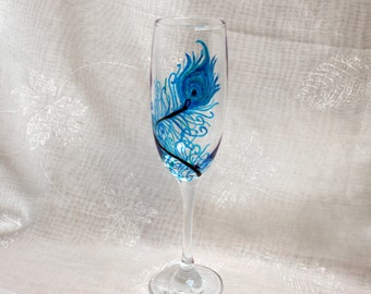 Peacock - An exclusive design, hand painted, large peacock feather encircling the bowl of a Champagne glass. In shades of blue & green.