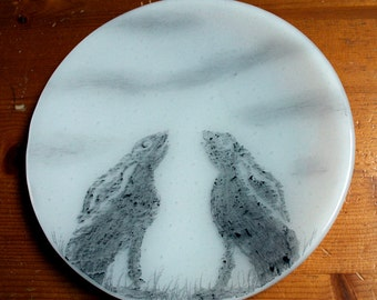 "Fused glass trinket plate 'Moon-Gazing Hare' A pair of hares sihouetted against a full moon with wispy clouds. Approx. 19 cm / 7.5"" diameter"