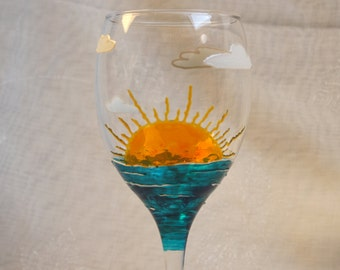 Sunshine. Exclusive design, hand painted, wine glass featuring a rising sun, the sea, clouds & around the base the words You are my Sunshine
