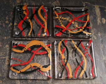 Fused glass coasters. 'Serpentine - Inferno'  Black, red and Gold on a clear base. Squiggly coasters. Choose 2 or 4. Can be customized.