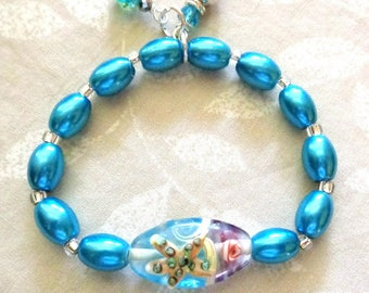 SALE: Beachy teal bracelet, starfish, lampwork, teal g;ass beads. stretch Bracelets, dangles