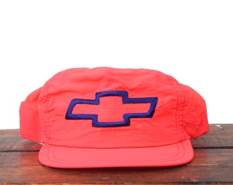 d1be159302066 Vintage Neon Pink Red Chevrolet Chevy Trucks Cars Racing Bowtie Logo  Trucker Hat Snapback Baseball Cap Made In USA