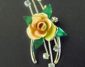 A gold tone Horseshoe brooch with pretty pink rose accent.  It also is accented with tiny crystals or rhinestones