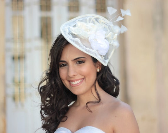 Ivory and white romantic hatinator with silky flowers and feathers for brides and special ocasions