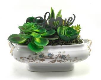 Faux succulent plant arrangement in vintage blue floral china gravy boat and die-cut 'Love'