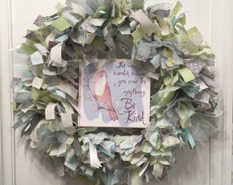 "rag wreath fabric and ribbon round 14"" metal frame MDF sign with bird ""In a world where you can anything Be Kind"" hangs in center"