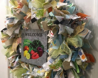 "rag wreath fabric and ribbon vegetable farmer's market theme round 14"" metal frame galvanized tin sign ""Welcome"" hangs in center"
