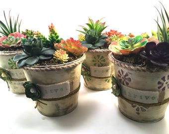 Choice faux succulent plant arrangement in chalk painted distressed metal container with jute rope and stamped canvas details