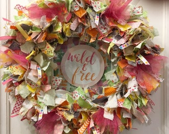 """SOLD on EBAY. rag wreath fabric and ribbon round 14"""" metal frame bright colors 2D 'Wild & Free' framed art hangs in center"""