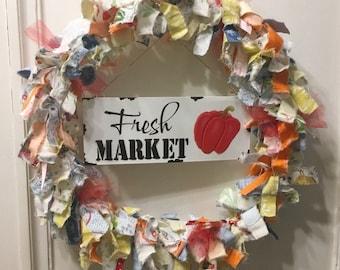 "rag wreath fabric and ribbon vegetable farmer's market theme round 14"" metal frame white enamel tin sign ""Farmer's Market' hangs in center"