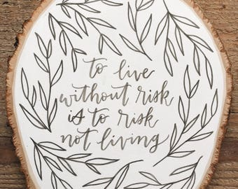 To live without risk is to risk not living - wood slice sign