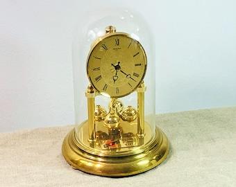 "Vintage 1984 Bulova Germany Quartz Brass Anniversary Clock, Glass Dome, Sphere Pendulum, Serviced, Vintage Condition. 9"" H. 6"" Base."