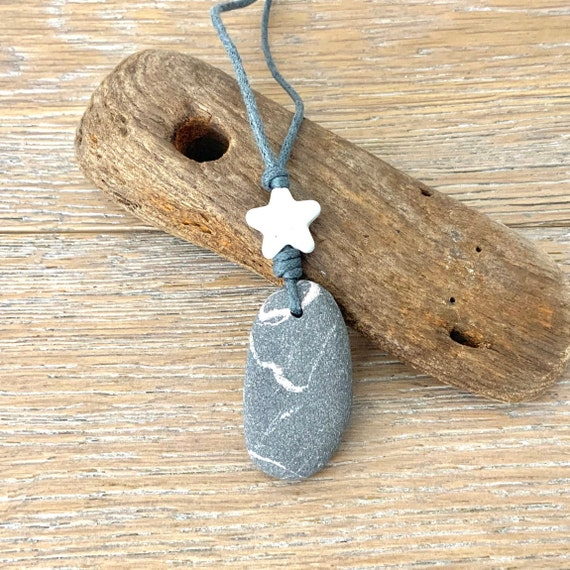 Raw stone star pendant necklace handmade using a natural beach stone and a ceramic star on an adjustable grey waxed cotton cord