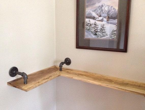 Reclaimed wood corner shelf with steel pipe brackets