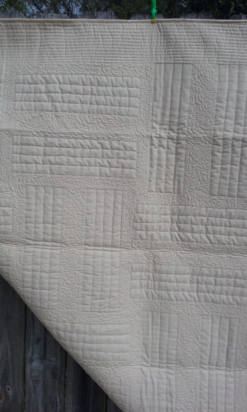 Quilt of beige brown and turquoise string pieced panels on a beige background