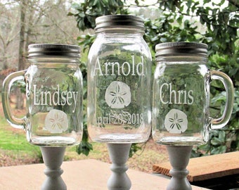 Sand Dollar Unity Sand Set Personalized Mason Jars atop Distressed White Wood Stands Names Date  Ceremony Toasting Glasses Beach Wedding