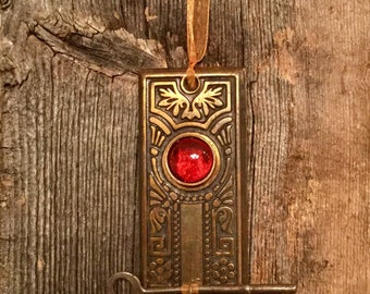 A vintage metal doorknob back plate combined with a skelton key from the early 1900's make up this unique hanging decoration.