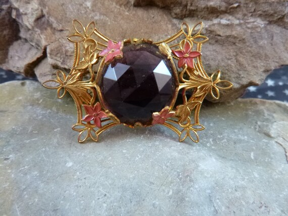 Mid Century Gilded Brooch Large Faceted Purple Glass Stone Surrounded by Pink Flowers and Golden Vines