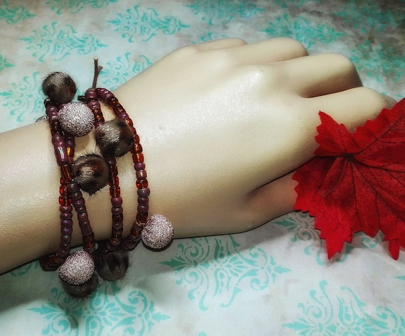 Wrap bracelet with pompoms by GunaDesign