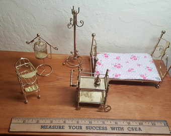 Brass dollhouse furniture set includes all the essentials: A comfy bed, a cradle, a bird cage, a decanter set, and a rocking chair