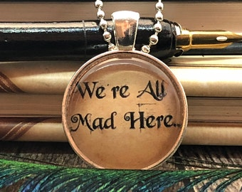 """Alice in Wonderland """"We're All Mad Here."""" set in Silver Dome Glass Pendant with Beaded Chain Necklace"""